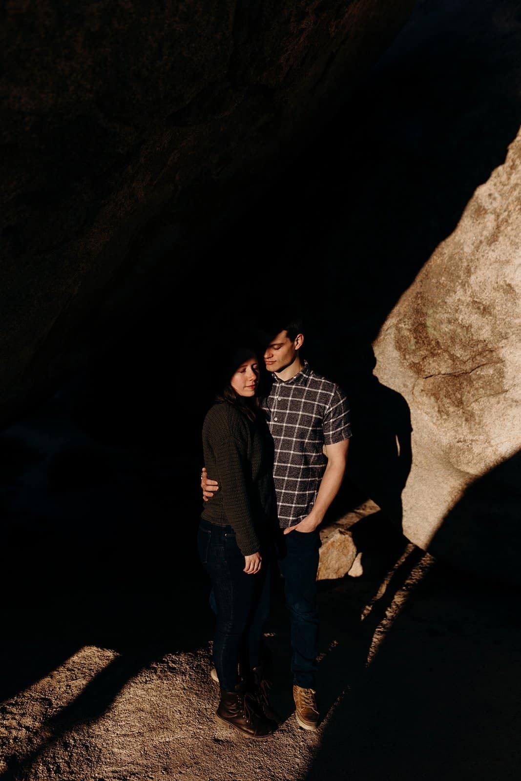 Shadowy photo of couple in cave in Joshua Tree National Park