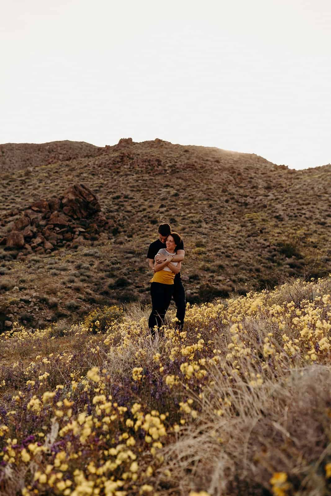 couple pose in super bloom on Trail on Fortynine Palms Oasis hike in Joshua Tree