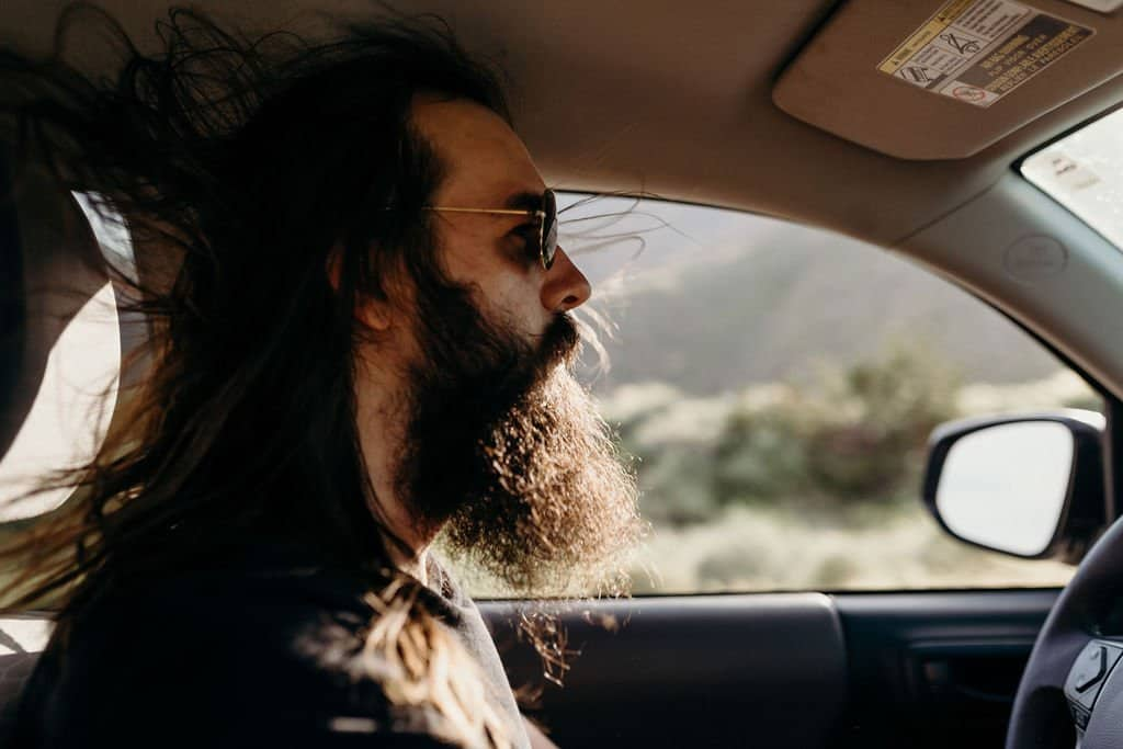 mans hair blowing in wind along southern california highway