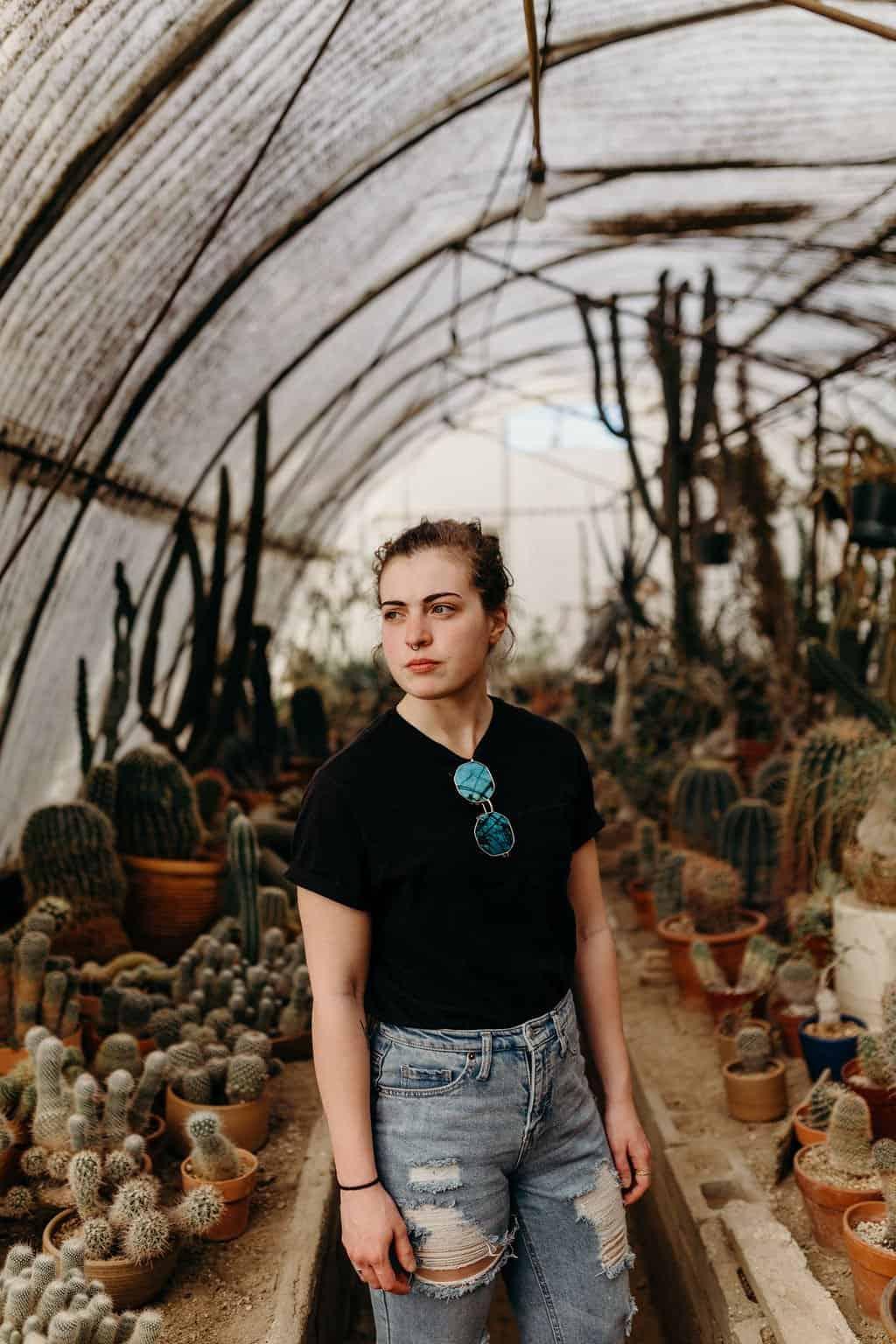 woman posing in greenhouse at moorten botanical gardens