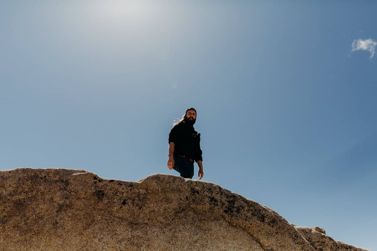 man climbing boulders in Joshua Tree National Park