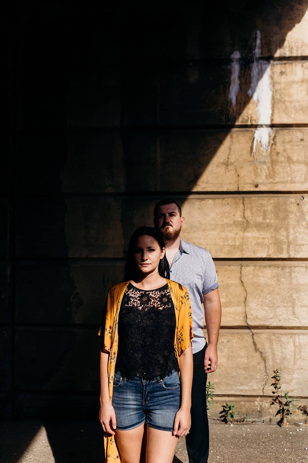 engaged couple standing at underpass looking at camera with weird shadows in Pittsburgh