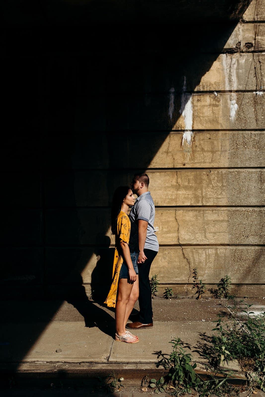 funky triangle shadows with engaged couple posing at underpass in Pittsburgh