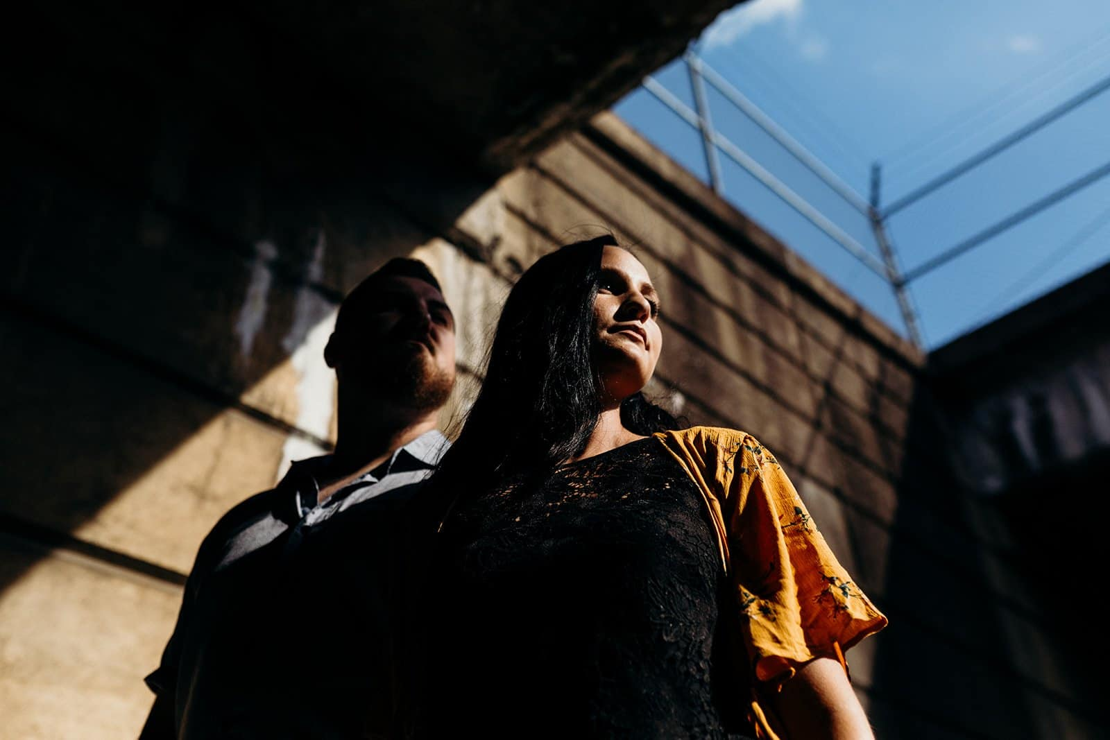 engaged couple in shadows of underpass looking to the right in Pittsburgh