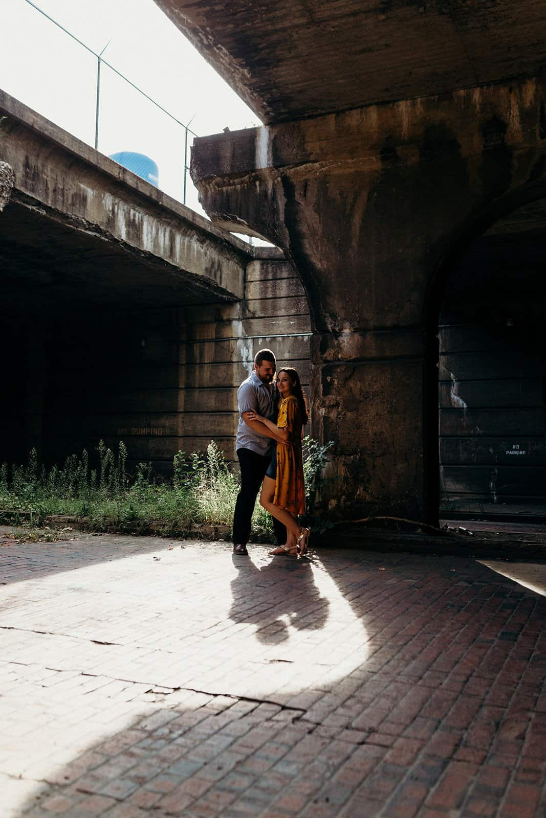 Couple hugging and smiling at underpass in Pittsburgh