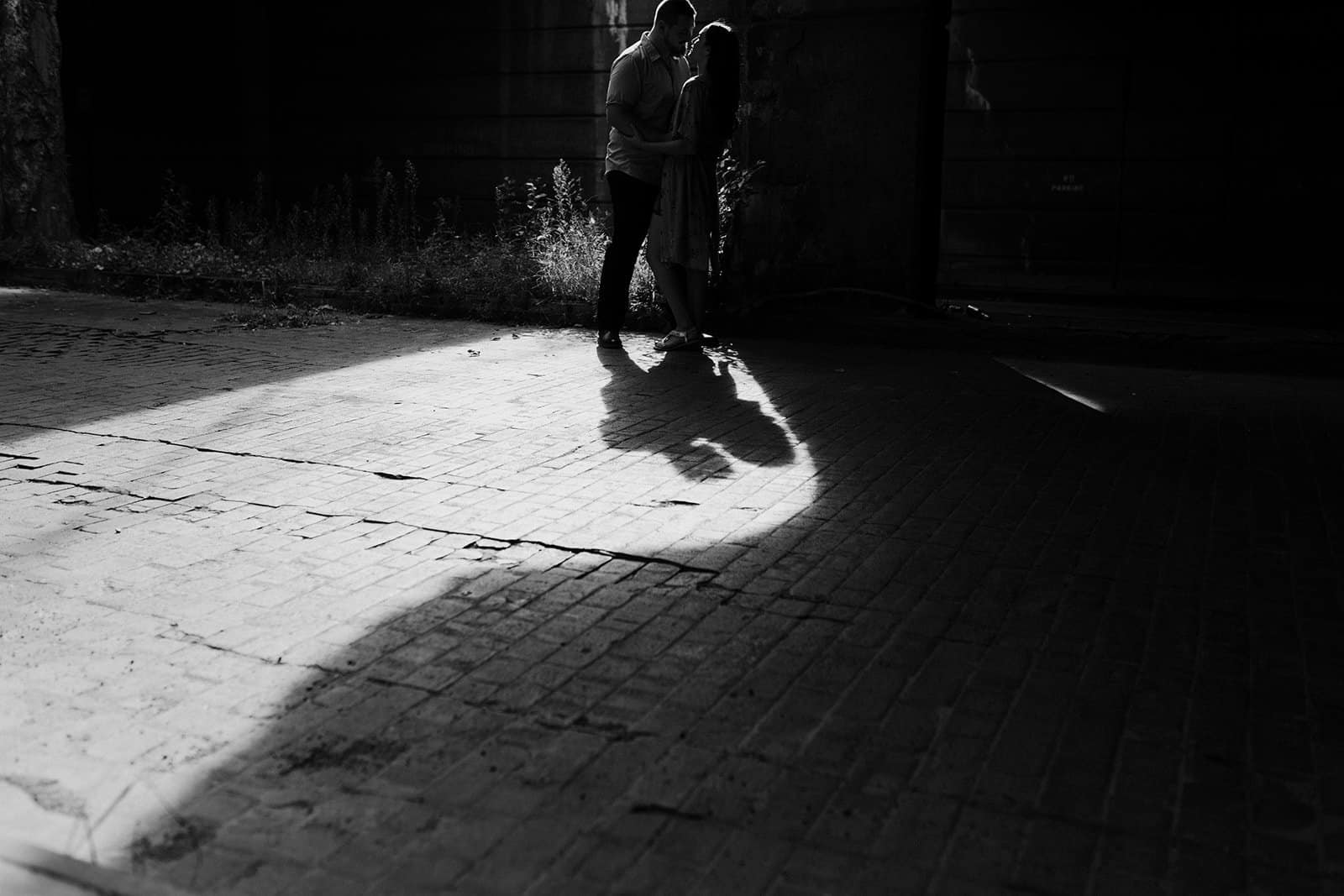 shadow of couple in distance embracing at underpass in Pittsburgh