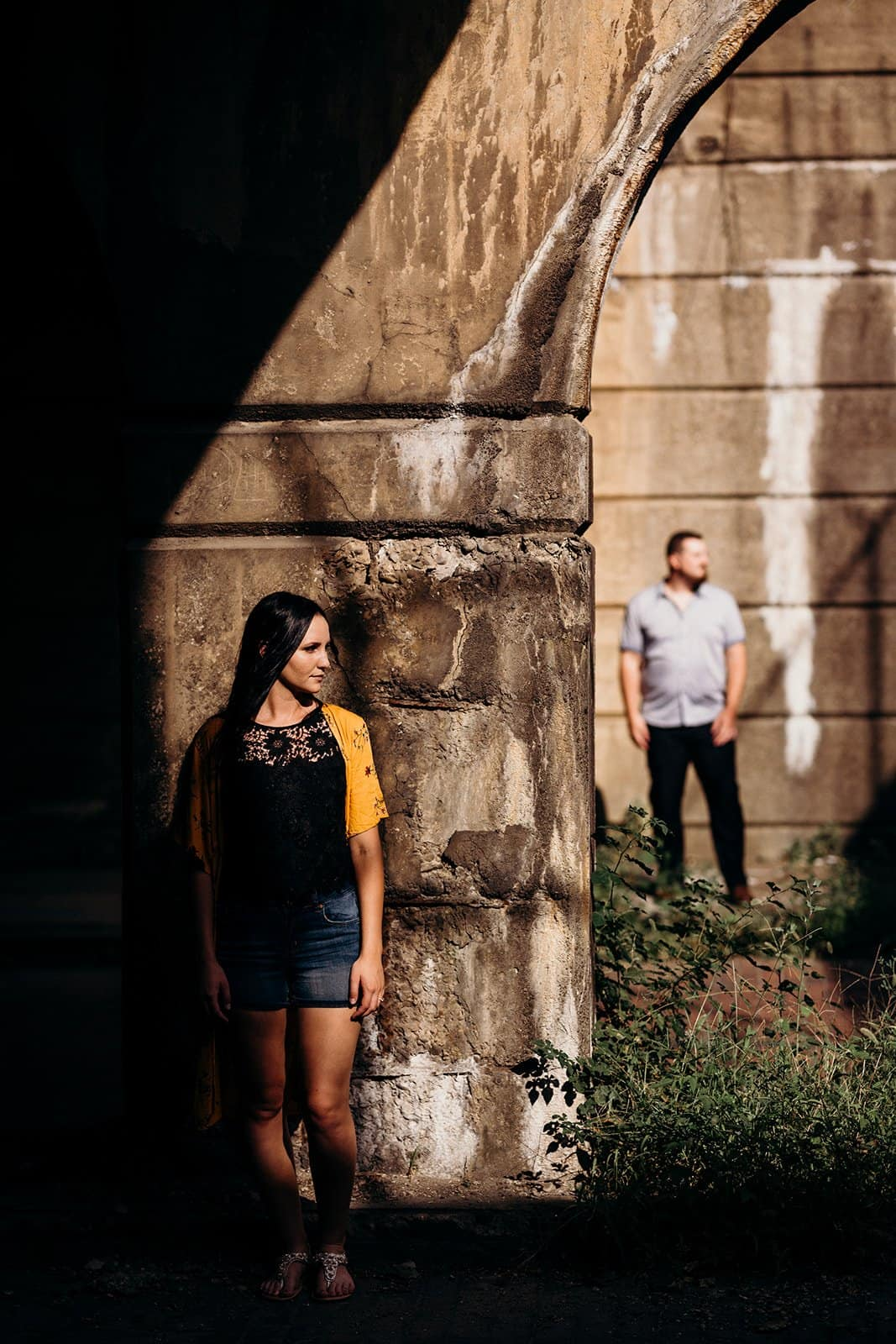 Couple standing in shadows at underpass in Pittsburgh