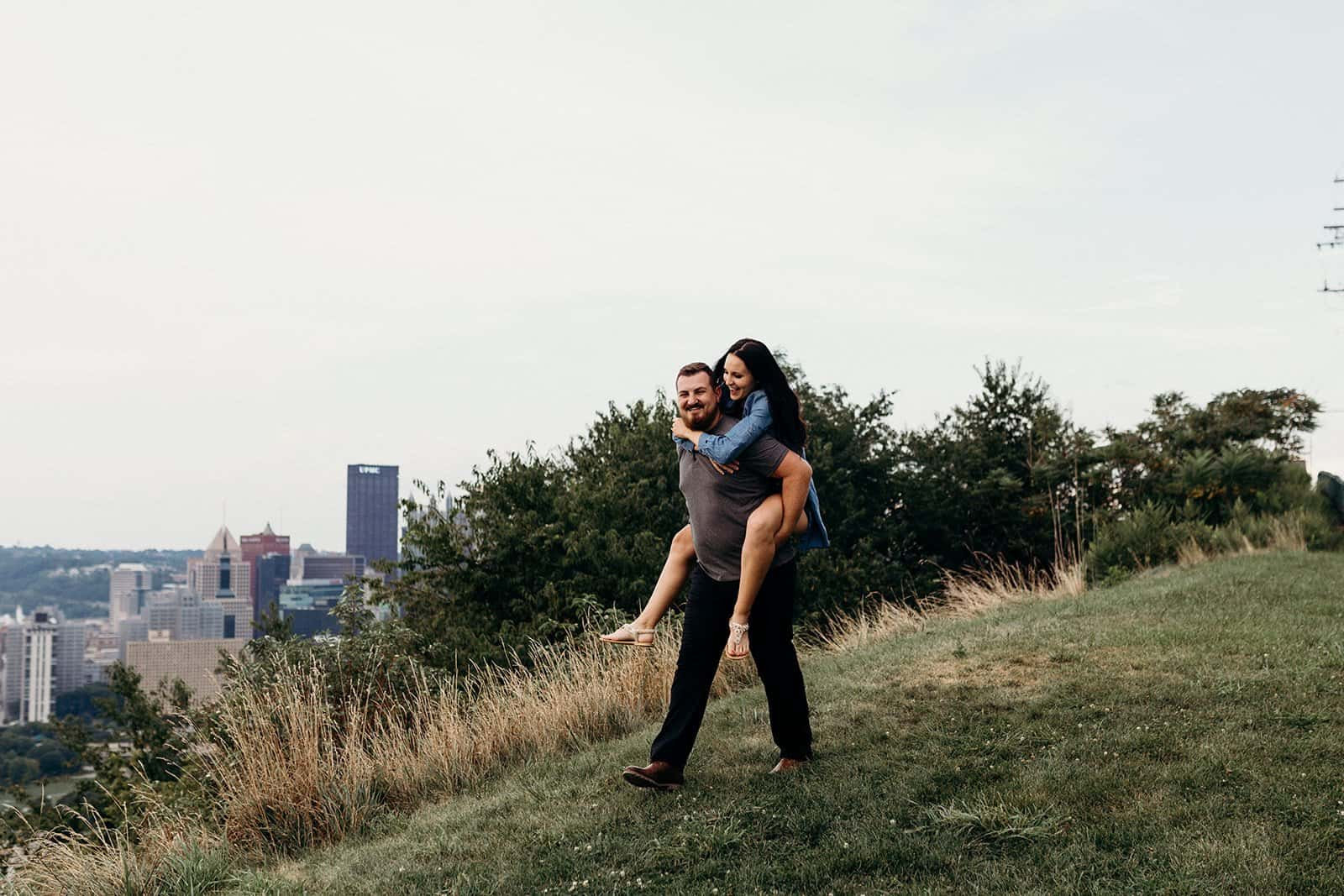 Couple laughing during piggy back ride on Mount Washington hillside in Pittsburgh