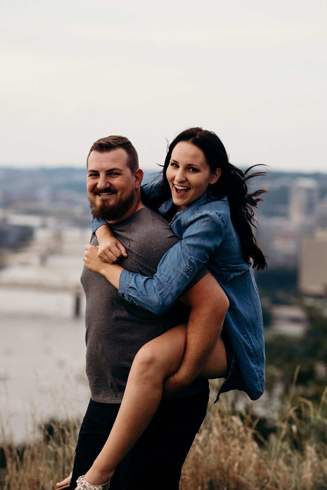 couple having piggy back ride with horizon of Pittsburgh in background