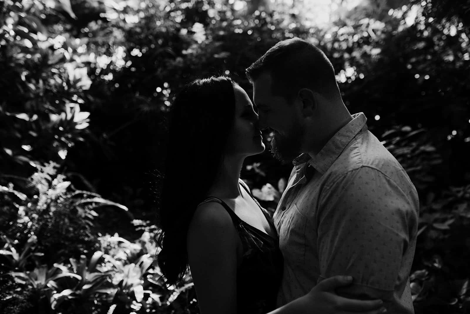 black and white photo of couple kissing in shadows at Phipps Conservatory engagement session
