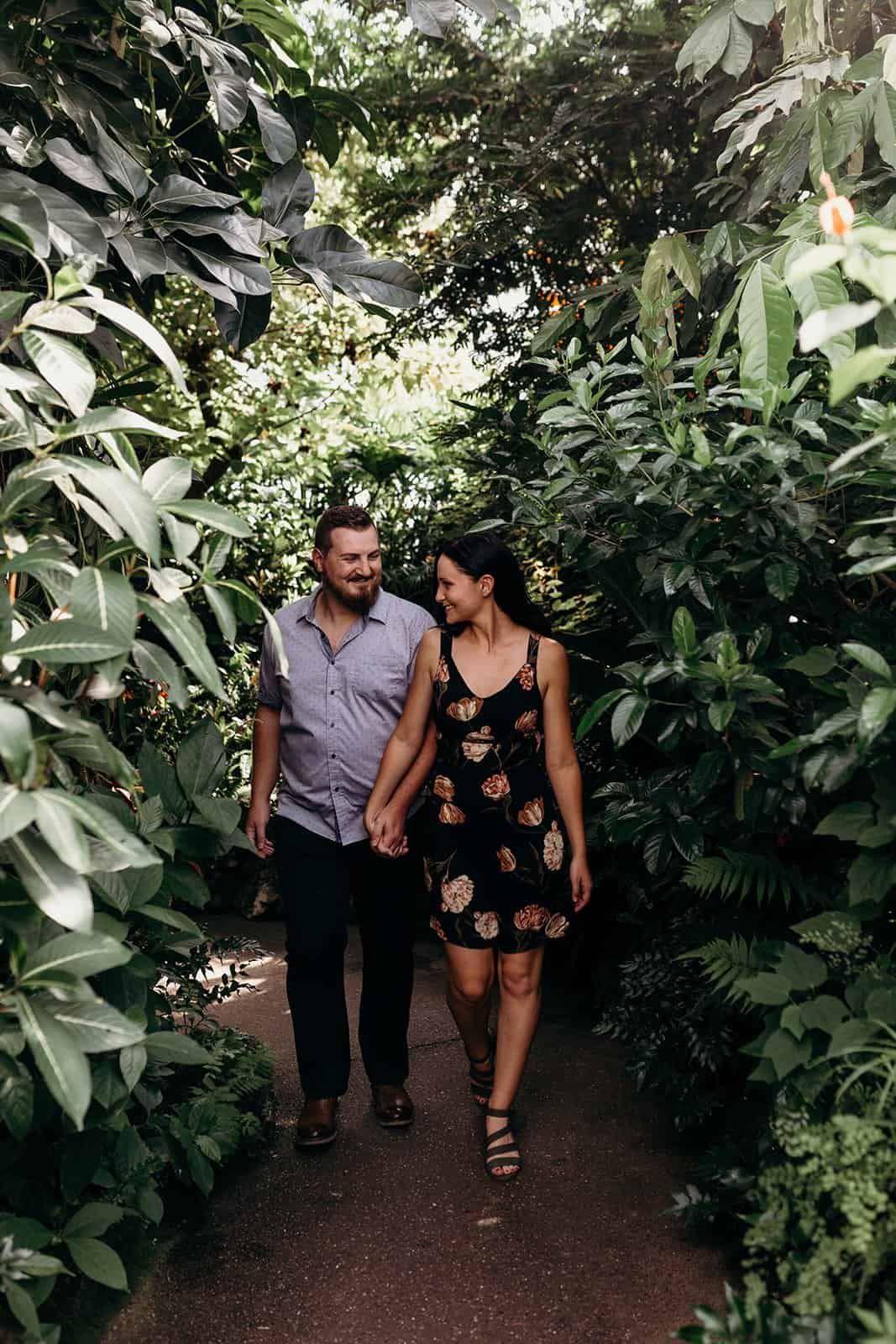 Couple smiling and holding hands while walking through greenery of Phipps Conservatory