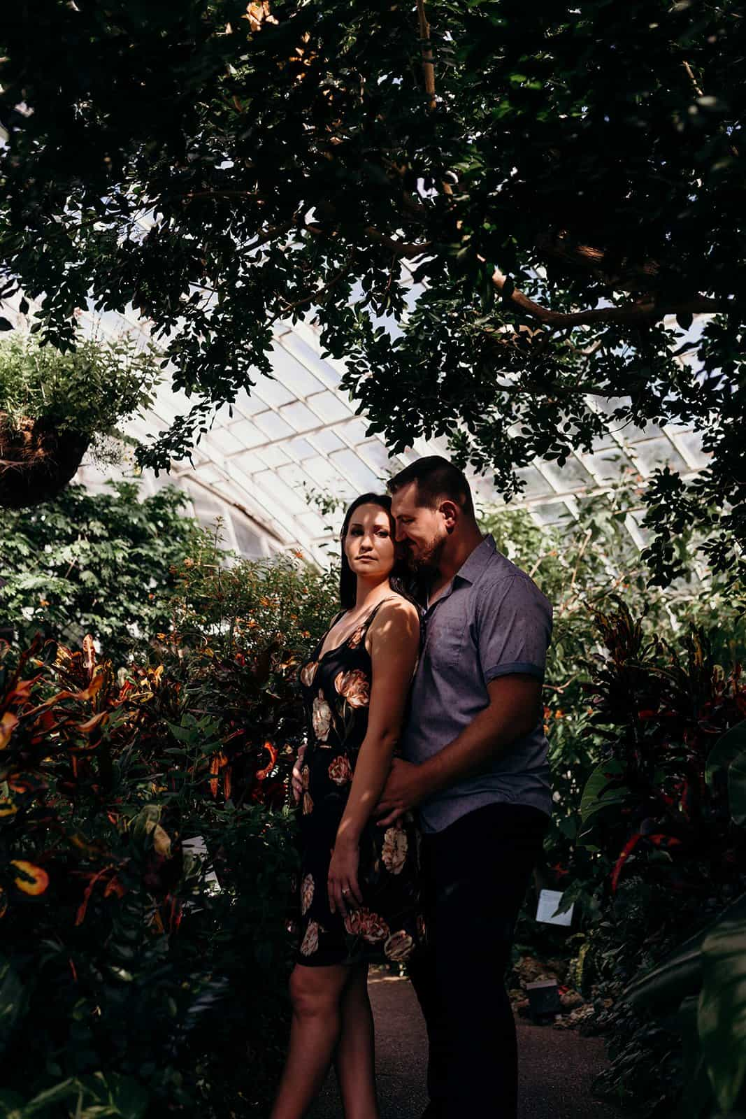 couple pose among plants in dappled light of greenhouse at Phipps Conservatory