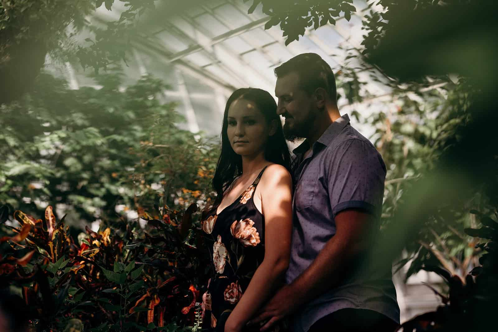 couple embrace through plants in greenhouse at Phipps Conservatory