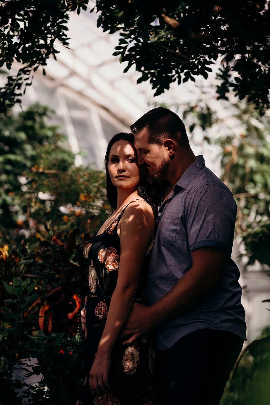 couple embrace in dappled light of greenhouse at Phipps Conservatory