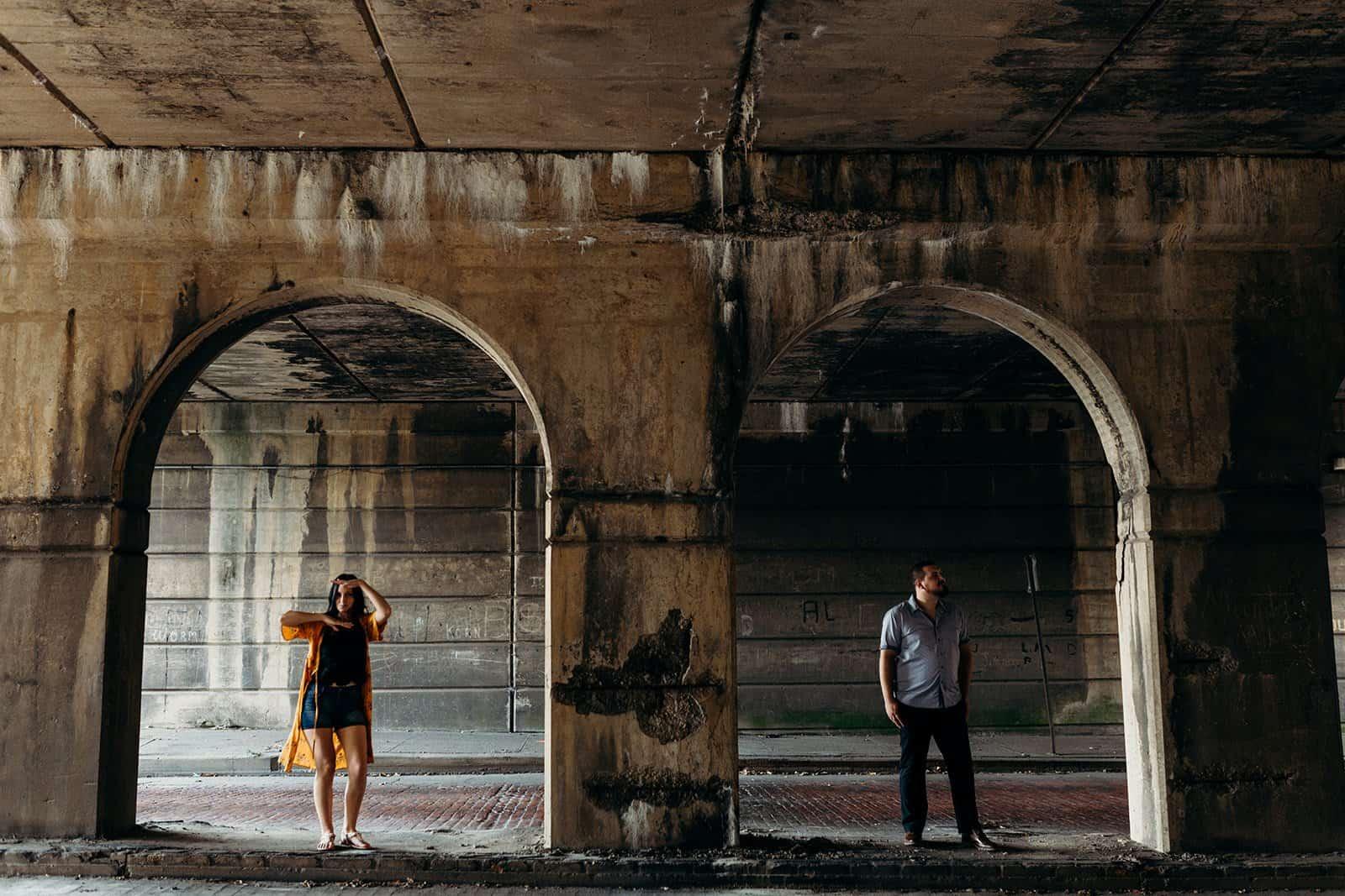 funny photo of couple posing in between pillars at underpass in Pittsburgh