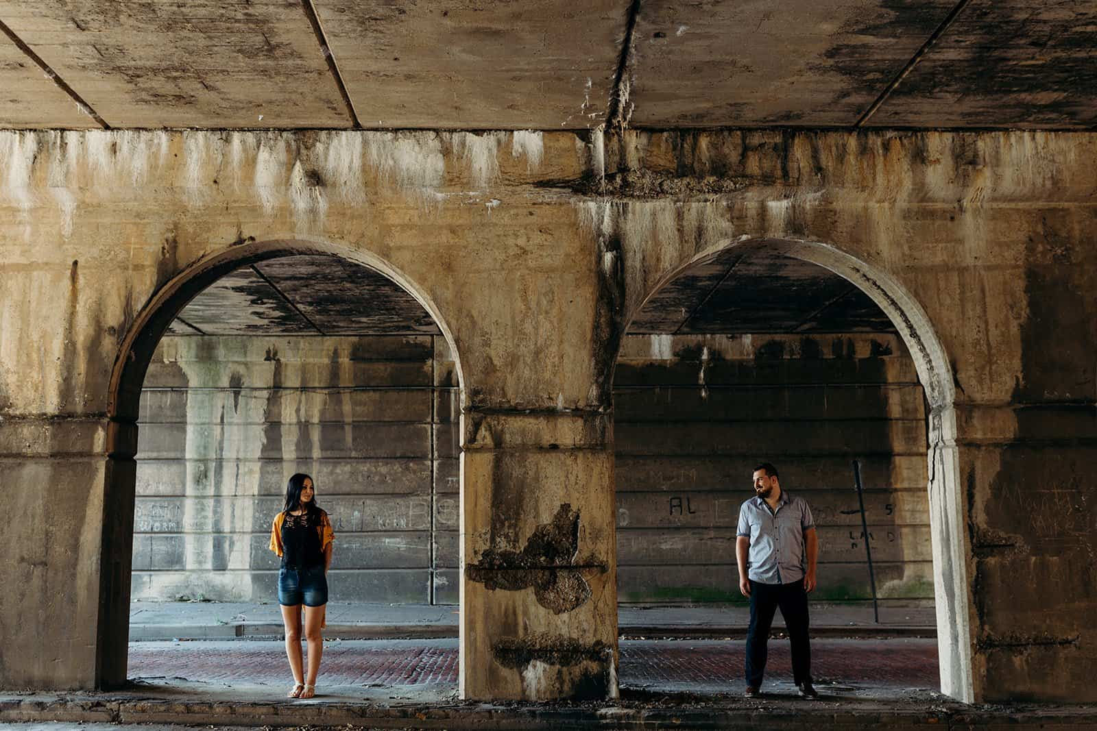 couple posing in between pillars at underpass in Pittsburgh