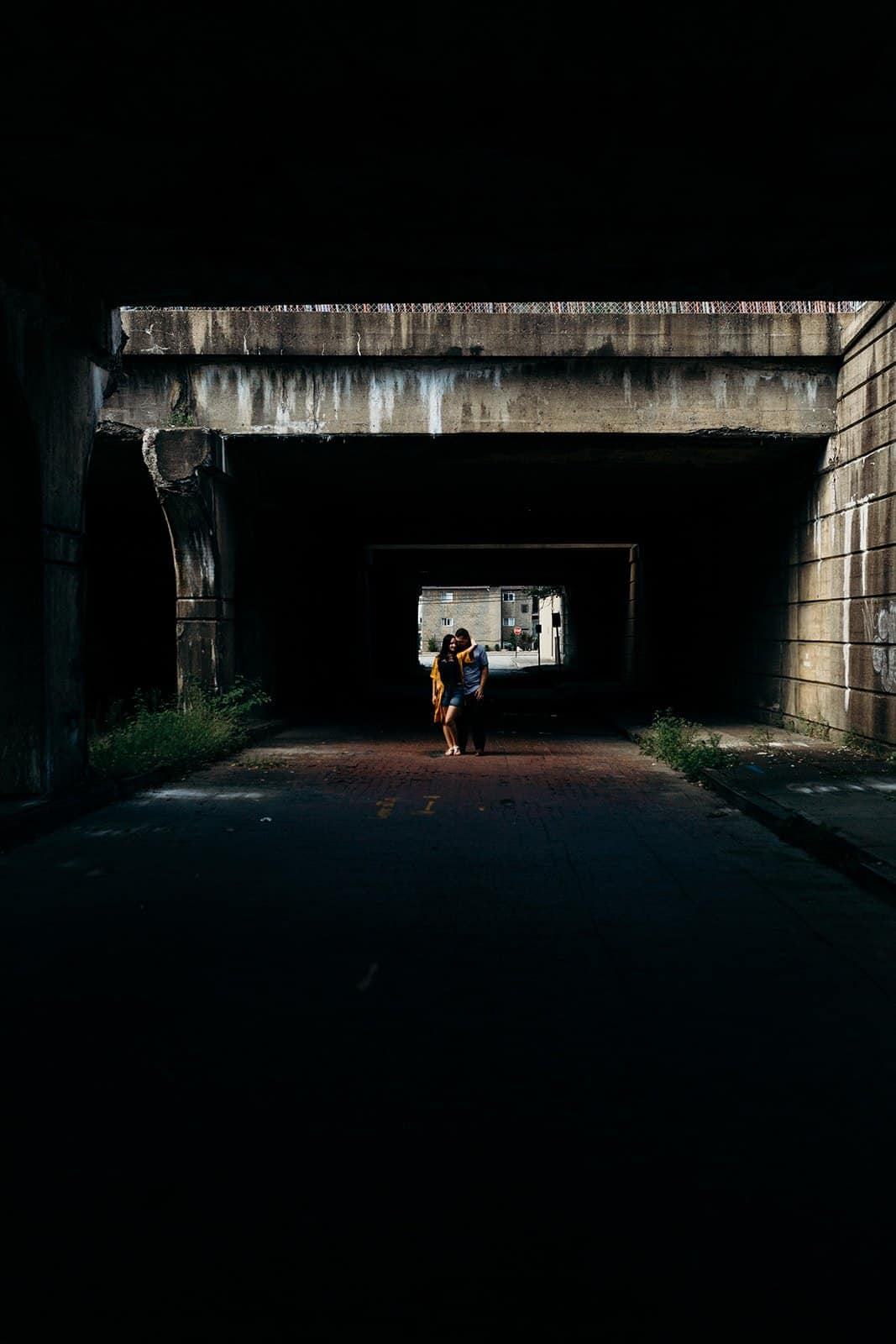 vertical photo of couple embracing at underpass in stream of light in Pittsburgh