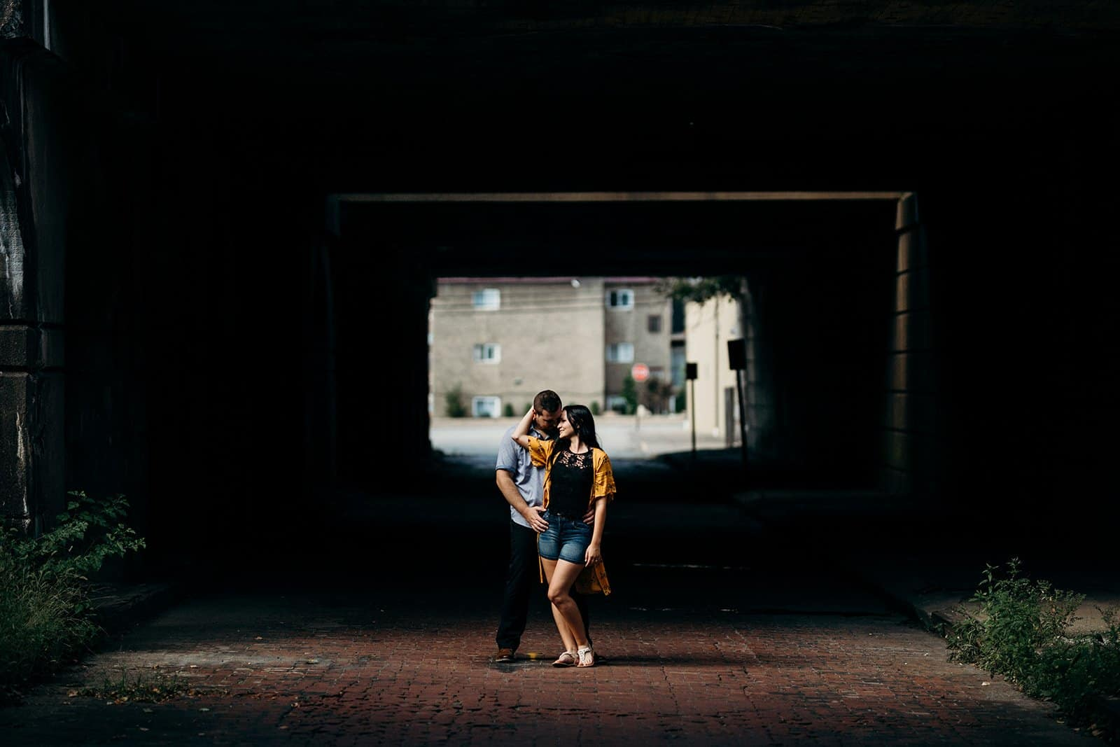 couple embracing at underpass in stream of light in Pittsburgh