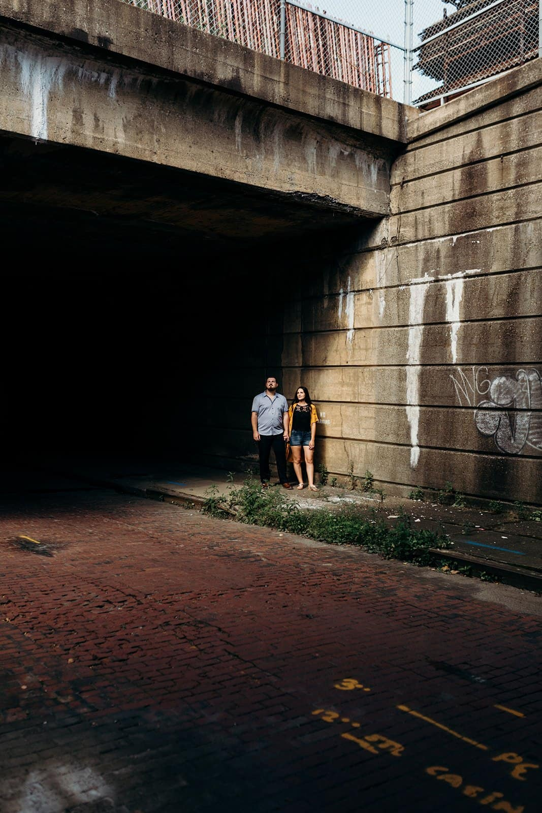 engaged couple looking into the sun at underpass with brick road in Pittsburgh